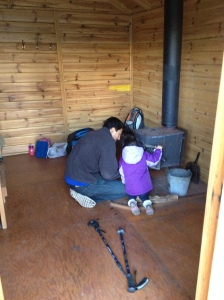 Our daughter assisting my husband in starting the (very small) stove fire.